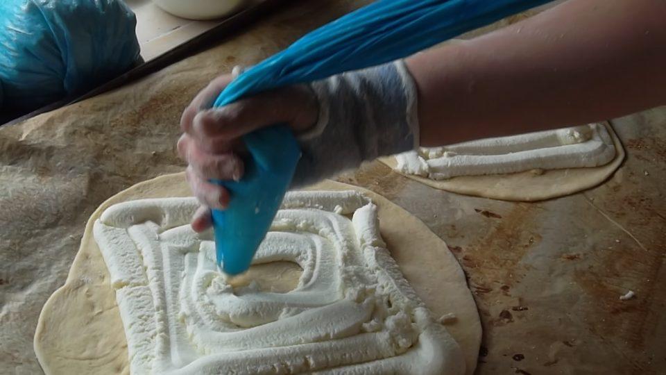 Náplň se na koláč rozprostře tak, aby okraje těsta zůstaly zčásti volné