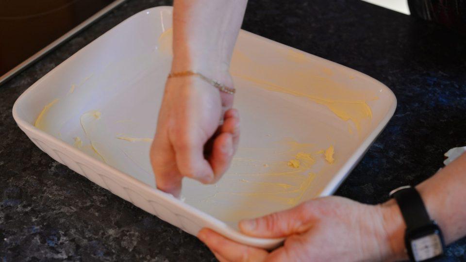 Zapékací mísu vymažeme máslem a vysypeme moukou