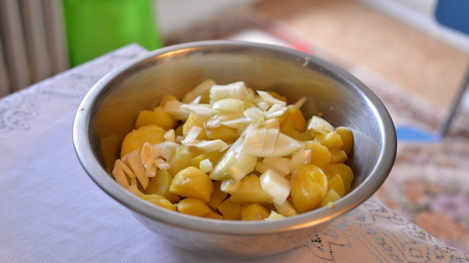 Brambory smícháme s cibulí, přidáme sůl, 3 lžíce sladké mleté papriky a zalijeme zálivkou