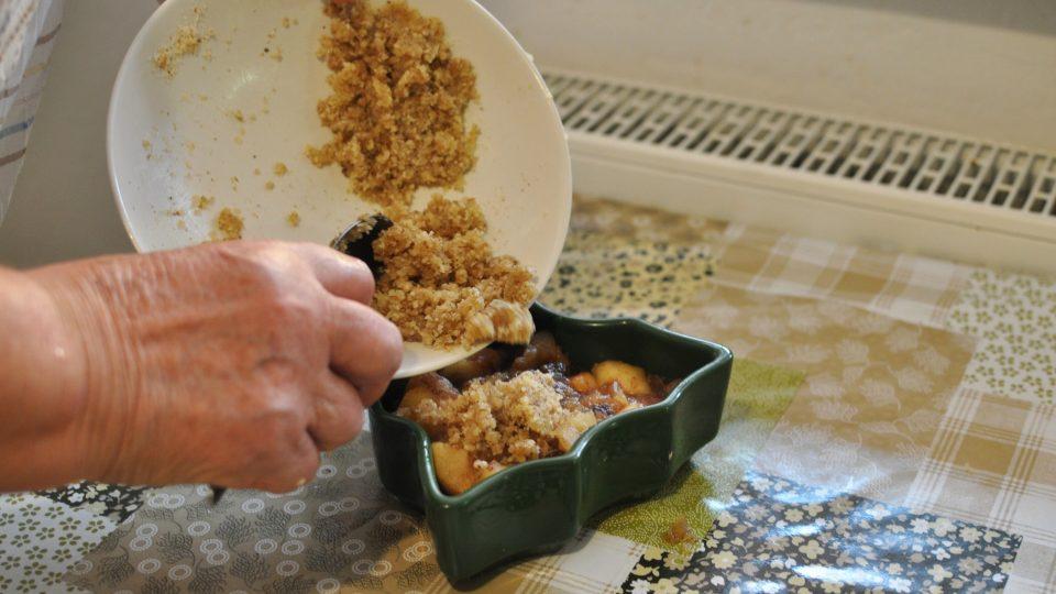 Připravenou směs dáme do formy vymazané máslem a zasypeme centimetrovou vrstvou drobenky