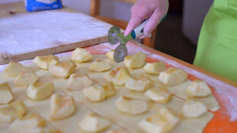 Rádýlkem placku rozdělíme na pruhy široké asi 10 cm, na které vyskládáme v pravidelných rozestupech osminky jablek a pak odkrajujeme čtverečky těsta i s jablkem