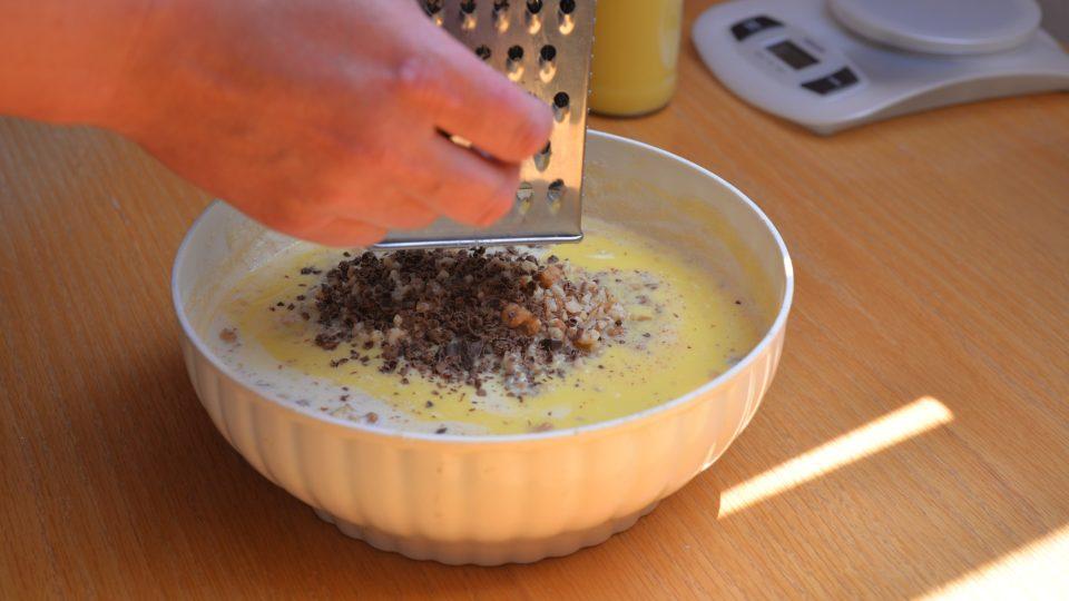Nakonec přidáme najednou 3 lžíce mléka, nasekané oříšky, mletý badyán, vaječný koňak a nastrouháme čokoládu. Vše spojíme do hladkého těsta
