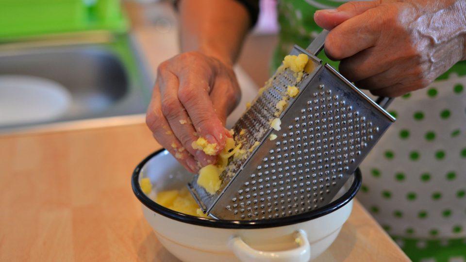 Uvařené brambory necháme vychladnout, oloupeme je a nastrouháme