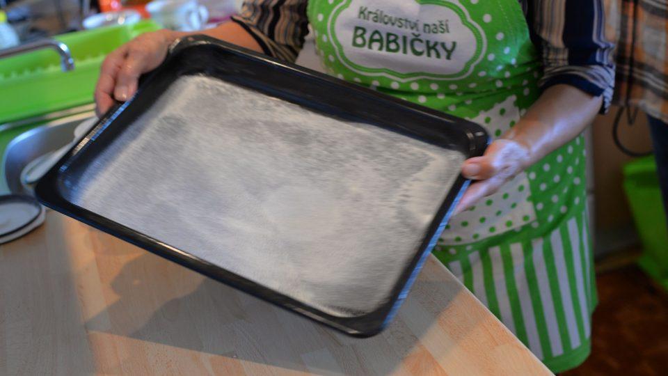 Plech na pečení vymastíme sádlem nebo máslem a posypeme polohrubou moukou