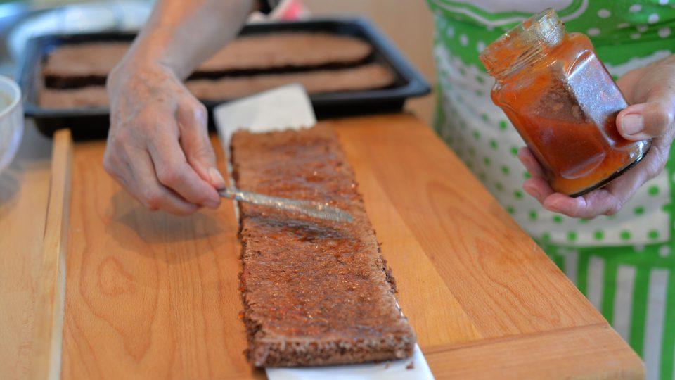 Těsto potřeme nejprve marmeládou, aby se krém nevpíjel do těsta, pak potřeme připraveným krémem
