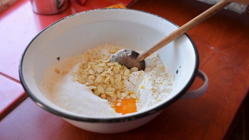 V míse smícháme mouku, pískový cukr, sůl, rozinky, mandlové plátky, nastrouhanou kůru z poloviny citronu, sáček vanilkového cukru