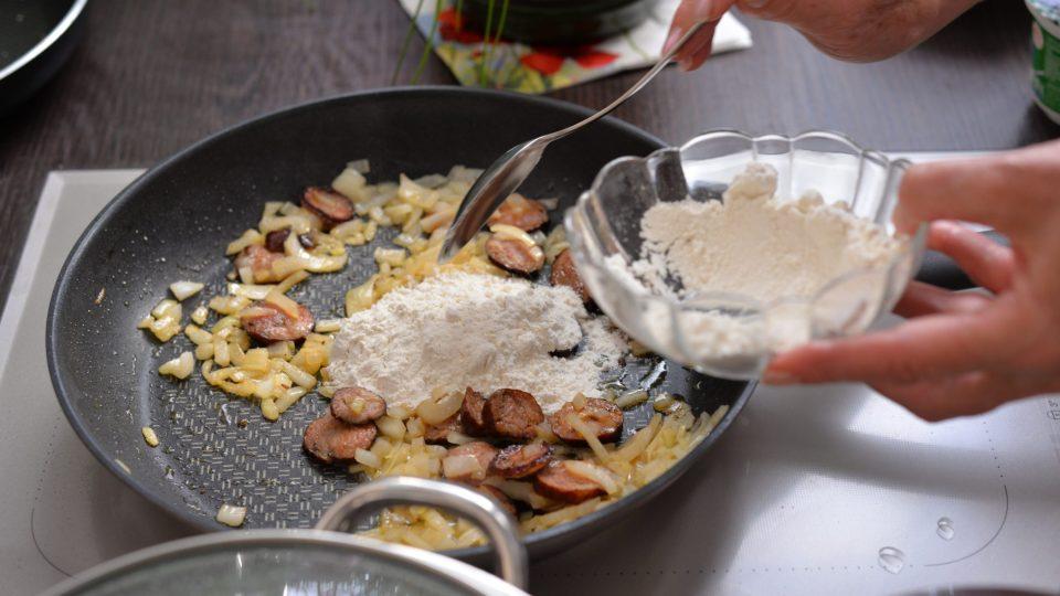 Po orestování zasypeme směs 3 lžícemi hladké mouky a uděláme cibulovo-klobásovou jíšku