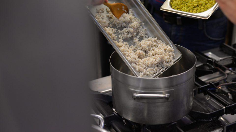 Následně ve větším hrnci smícháme uvařené kroupy, uvařený hrách a osmaženou cibulku s česnekem