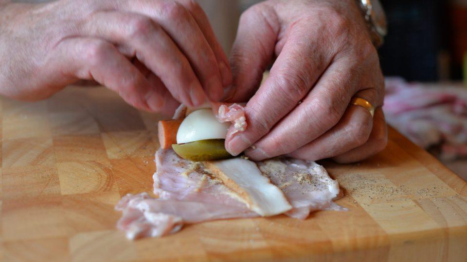 Na okořeněný plátek masa položíme tenký plátek slaniny nebo špeku. Na jeden z okrajů k sobě přiložíme čtvrtku kyselé okurky, půlku párku a čtvrtku vejce