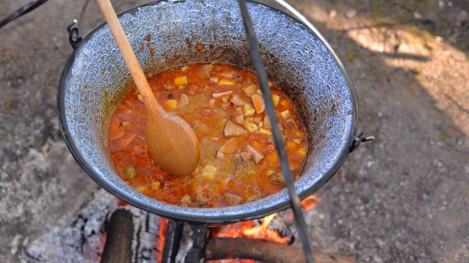 Zhruba půl hodiny před koncem přidáme na kostičky nakrájené syrové brambory, papriky a na půlkolečka nakrájené klobásy