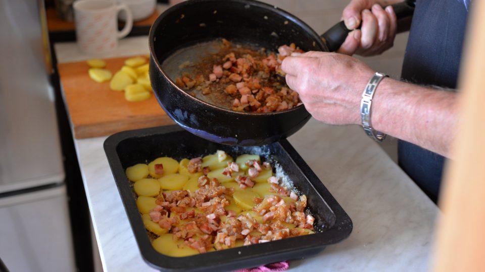 Na vrstvu brambor naklademe vrstvu cibule, škvarků a uzeného, kam jsme přidali i trochu namořených hub