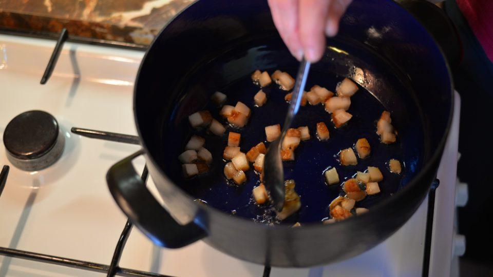 Slaninu nakrájíme na kostičky, dáme opéct do kastrolu na lžíci sádla, přidáme naloženou zeleninu